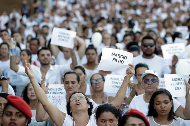 Friends and relatives hold signs with the names of victims, during a march paying homage to the victims of the mining dam collapse in Brumadinho, Brazil. Photo / AP