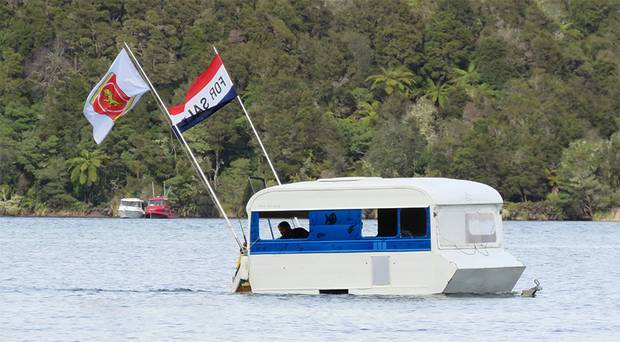 Anglers enjoying the opening of the fishing season on Lake Tarawera near Rotorua today spotted this unusual craft trolling for fish! One of the flags says For Sale. Photo / Supplied