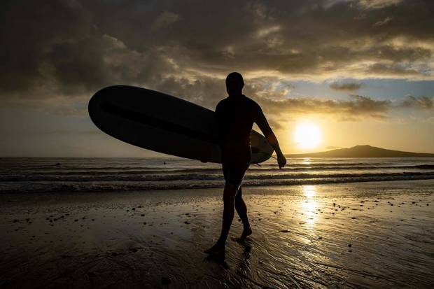 A man leaves Takapuna beach after a surf just after sunrise this morning. Photo / Supplied