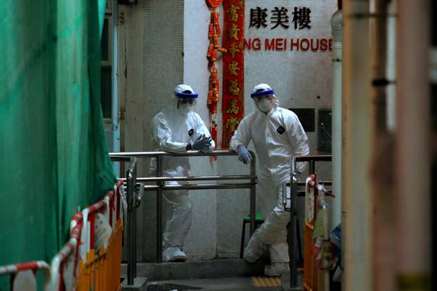 Personnels wearing protective suits wait near an entrance at the Cheung Hong Estate, a public housing estate during evacuation of residents in Hong Kong. Photo / AP