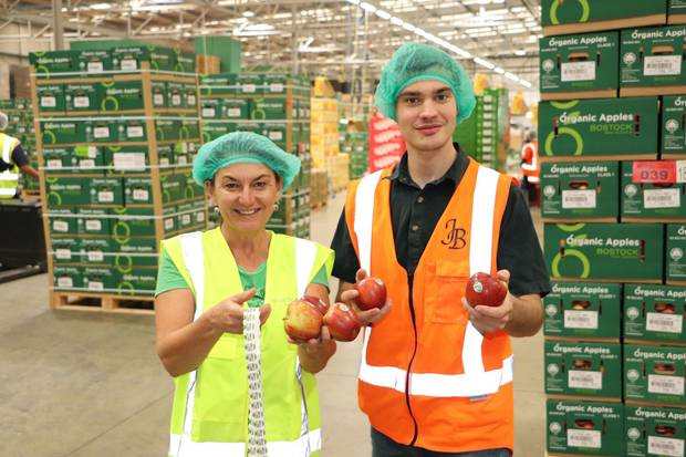 Heidi Stiefel and Tom Bostock proudly display apples with compostable stickers. Photo / Supplied