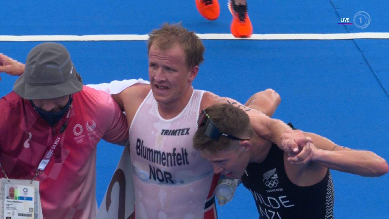 Bronze medallist Hayden Wilde of New Zealand helping gold medal winner Kristian Blummenfelt after the race. Photo / TVNZ/Sky Sport