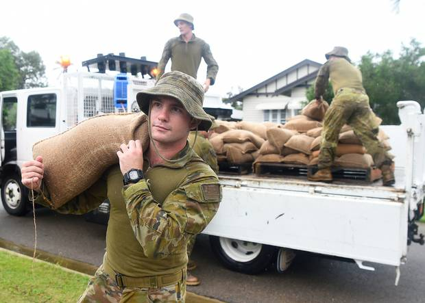 Australian soldiers from 3CER help deliver sandbags to Townsville residents in the suburb of Railway Estate. Photo / Getty