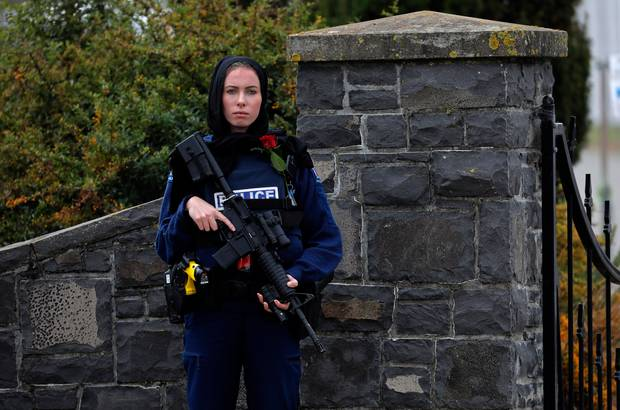 This powerful image of police officer Michelle Evans standing guard with a rose and a hijab has been shared widely. Photo / AP