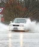 A car navigates its way through a flooded road in Ashburton. Photo / Ashburton Guardian