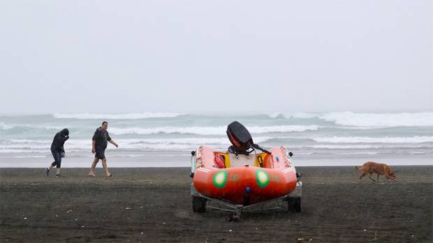 Bethell's Beach goers leave after a large down pour, the rain emptied the beach within minutes on Sunday afternoon. Photo / Greg Bowker