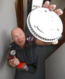 Bay of Plenty coast area fire risk management officer Bill Rackham installs a smoke alarm. Photo / File