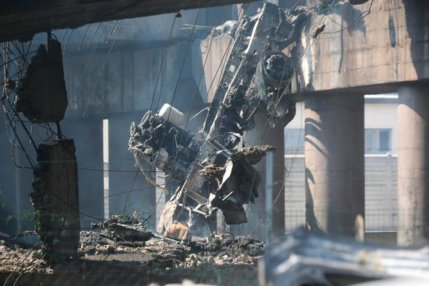 The charred remains of a truck are seen hanging from a partially collapsed overpass of the highway on the outskirts of Bologna, Italy.