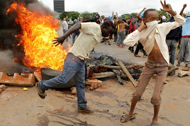Protestors gather near a burning tyre during a demonstration in Harare, Zimbabwe. Photo / AP