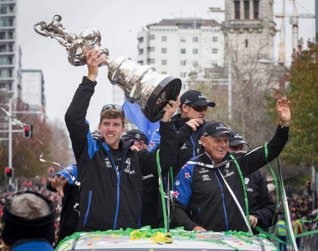 Team New Zealand's Peter Burling holds the Auld Mug with Glenn Ashby and Grant Dalton. Photo / Greg Bowker