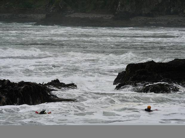 Surf lifesaving crews in the water searching around rocks for any sign of the missing man today. Photo / SLNZ