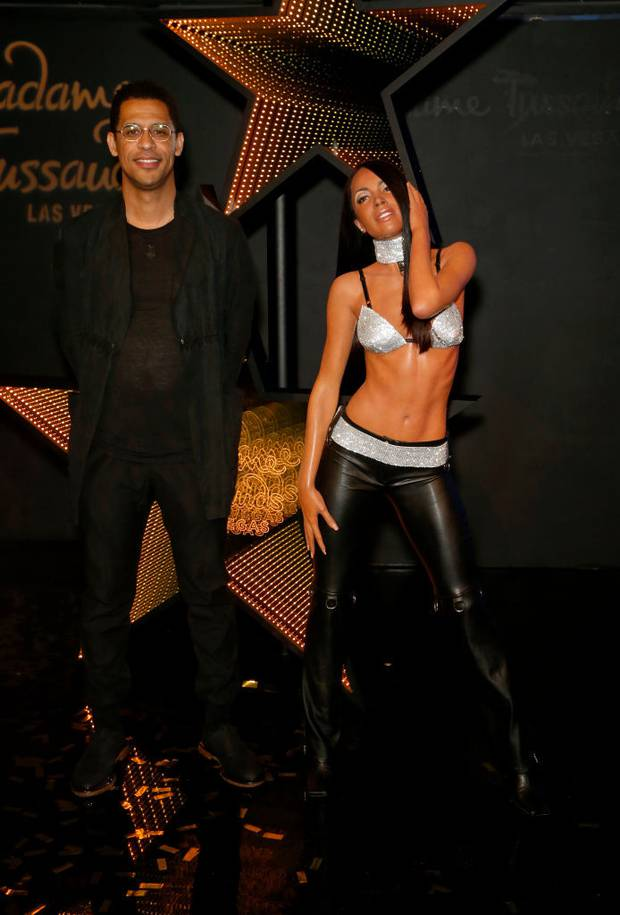 Rashad Haughton poses with a figure of his sister's wax figure Aaliyah during the unveiling. Photo / Getty Images