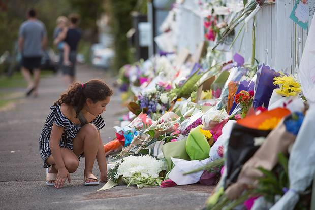 New Zealanders like 7-year-old Anna Burke-Pohiva, pictured outside the Ponsonby Mosque, have left flowers at mosques around the country since the Christchurch massacre. Photo / Chris Loufte