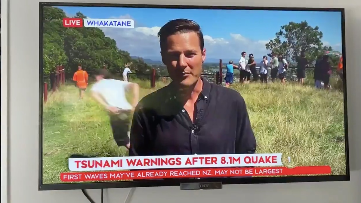 'He hits and he misses': Man tries to photobomb tsunami reside reporting, fails – NZ Herald