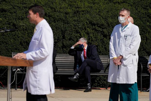 White House Chief of Staff Mark Meadows, seated centre, listens as Dr. Sean Conley, physician to President Donald Trump, briefs reporters. Photo / AP