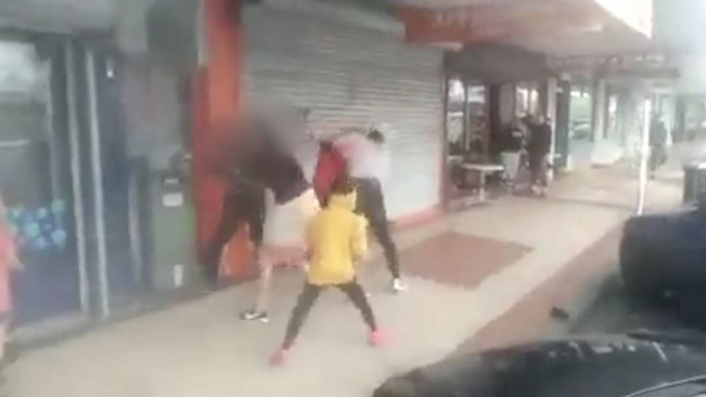 Four men fight as a child, in a yellow hoodie, also joins in the fray.