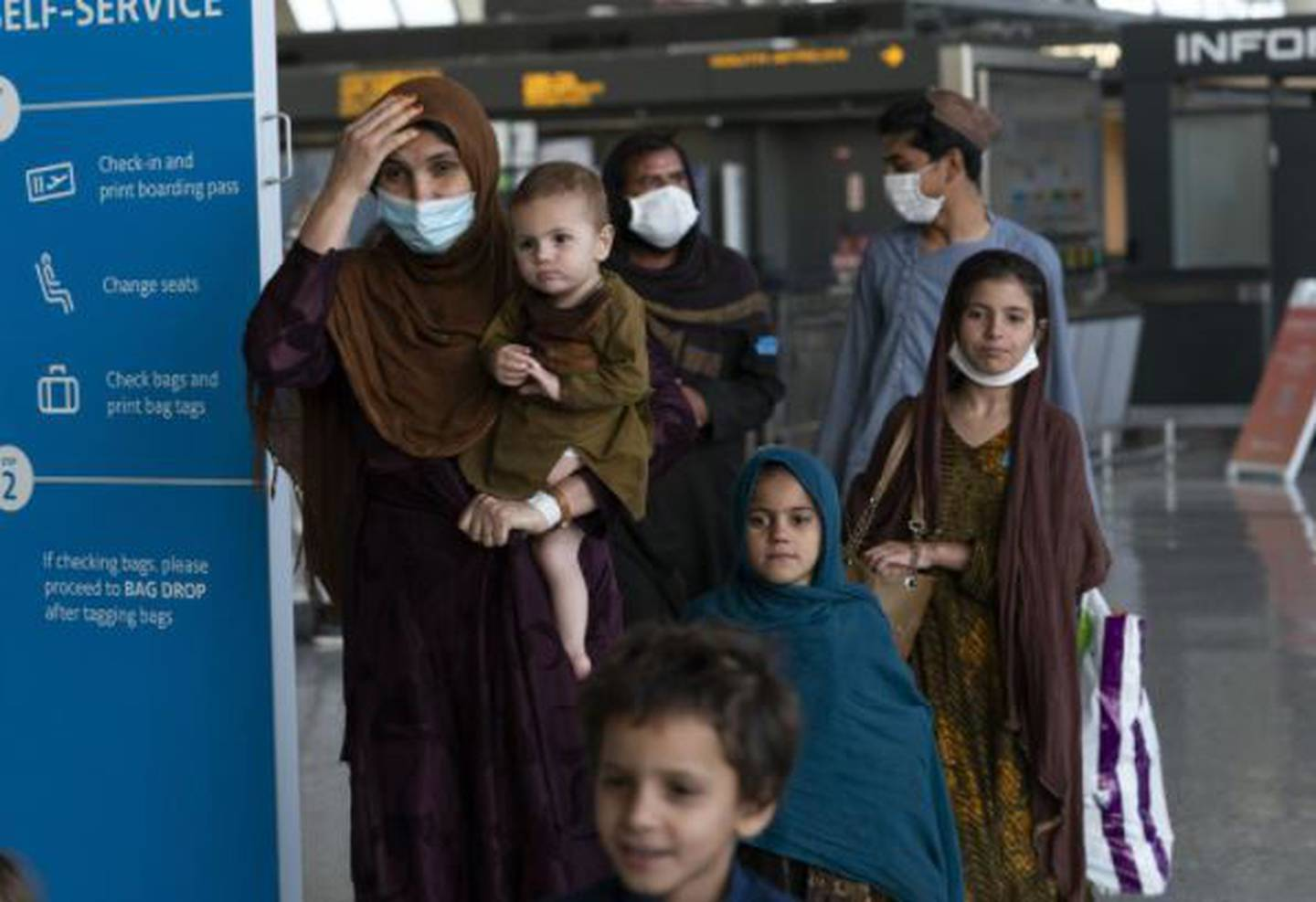 Families evacuated from Kabul, Afghanistan, walk through the terminal before boarding a bus after they arrived at Washington Dulles International Airport. Photo / AP