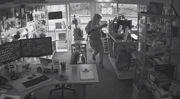 The man enters the store and takes off with two computers. Photo / CCTV