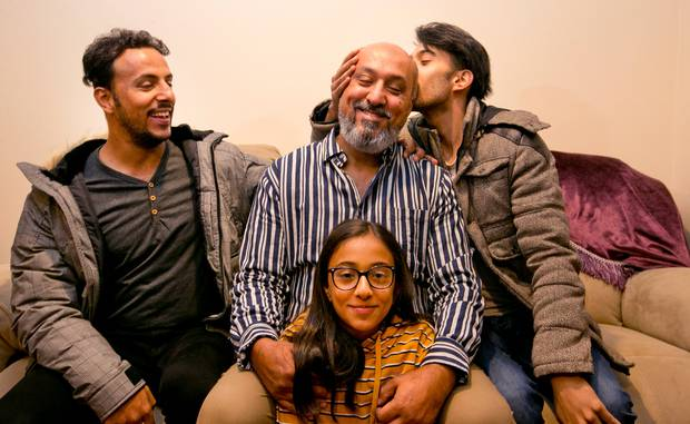 Khaled Al-Jammali gets a kiss from his son, Mahmoud Al-Jammali, right, while his other son, Hamoud Al-Jammali, left, and daughter Tala Al-Jammali are just happy to be with their fathero
