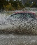 A car ploughs through surface flooding on Teviot St today. Photo / Otago Daily Times