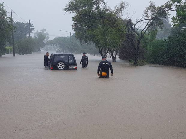 Police assist in the evacuation of residents in flood-hit Townsville