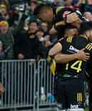 Hurricanes second five Ngani Laumape is swamped by jubilant teammates after scoring in the tackle of Lions first five Dan Biggar during their match at Westpac Stadium. Photo / Mark Mitchell