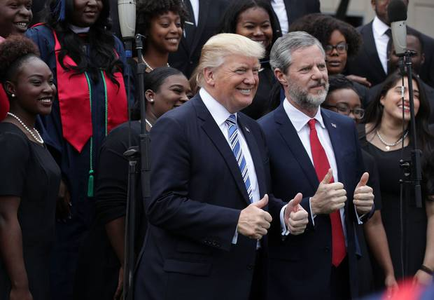 President Donald Trump (L) and Jerry Falwell (R), President of Liberty University, pose for photos with members of gospel choir in 2017. Photo / Getty Images
