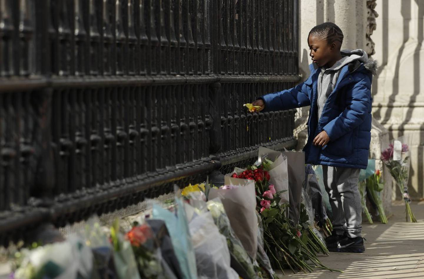 At Buckingham Palace a young boy places a flower on the Palace gate. Photo / AP