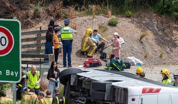 Emergency services attend to injured passengers after a tourist bus rolled on the Glenorchy-Queenstown Rd. Photo / James Allan