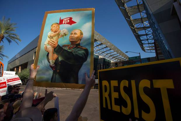 A protester with a poster of Trump and Putin outside the Phoenix Convention Center where Trump was holding a rally in August 2017. An FBI investigation was launched in May 2017. Photo / Getty