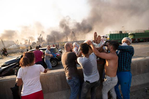 People evacuate wounded after of a massive explosion in Beirut, Lebanon. Photo / AP