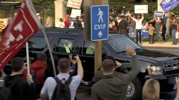 In this image from video, President Donald Trump waves as he drives past supporters. Photo / AP