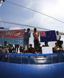 Sri Lankan asylum seekers hold signs and plead for assistance as they seek asylum to New Zealand in 2011. Photo / Getty Images