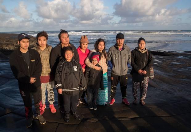 Family of the drowning victims Kay Dah Ukay, 48, and his wife Mu Thu Pa, 50, gather at Muriwai beach. Photo / Brett Phibbs