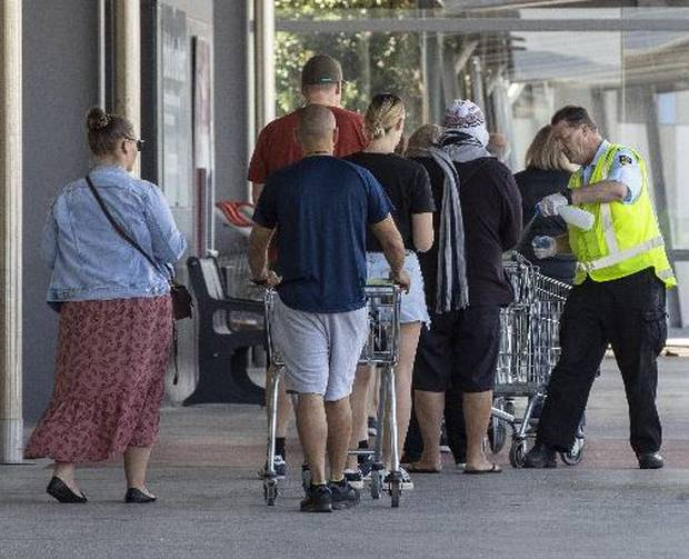 Security at Countdown Te Rapa, Hamilton, sanitises trollies of shoppers queued up on Wednesday. Photo / Mike Scott