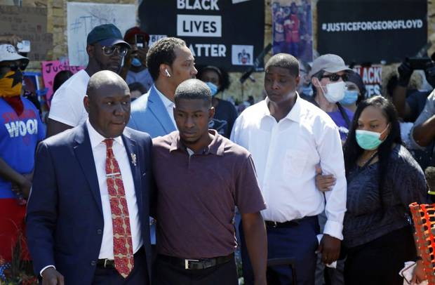Family attorney Ben Crump, left, escorts Quincy Mason, second from left, a son of George Floyd today as they and some family members visited a memorial where Floyd was arrested and died. Photo / AP