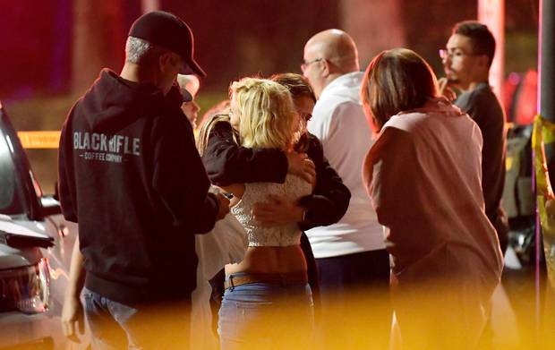 People comfort each other as they stand near the scene. Photo / AP
