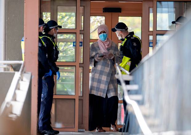 Police talk to a woman at housing commission apartments under lockdown in Melbourne. Photo / AP