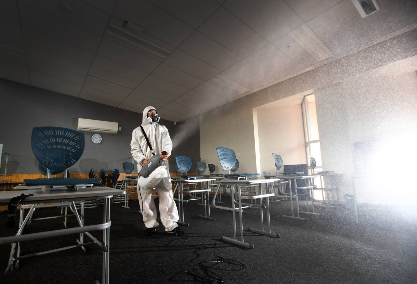 Mike Sommerville Managing Director of Sterico, sprays Zoono Z-71 microbe shield surface sanitiser at an Auckland school. Photo / Brett Phibbs