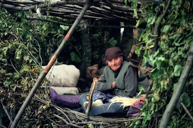 Një grua 94 vjeçare etnike shqiptare ulet në strehën e saj të degëve të pemëve.  Foto / Përplas Goddard