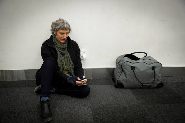 Susan Lamont sits on the floor to charges her phone from a power point at Auckland Airport's domestic terminal. Photo / Dean Purcell