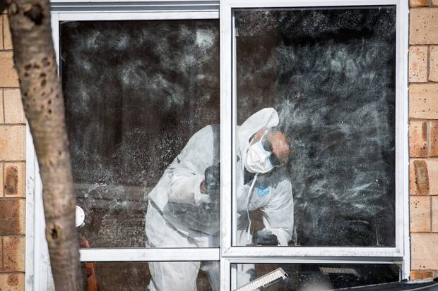 Forensic staff examine for fingerprints on the sliding door entrance to a garage which had recently been converted into another room at the house. Photo / Jason Oxenham