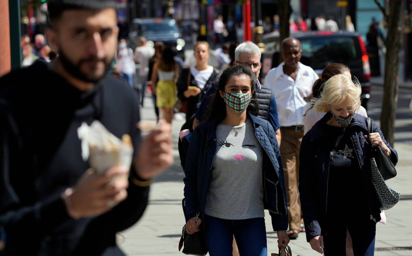 Two women walk along Oxford Street while wearing a face masks against the coronavirus in London on August 6. Photo / AP