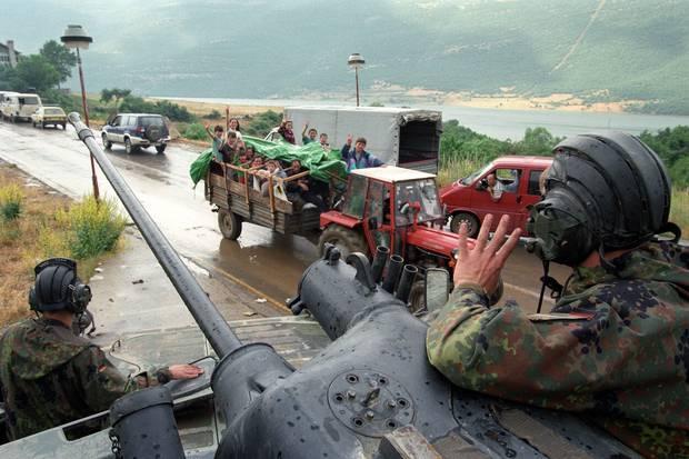 Kosovarët valëviten në trupat gjermane të NATO-s për kthimin e tyre në Kosovë në kalimin kufitar të Morinit.  Foto / Përplas Goddard
