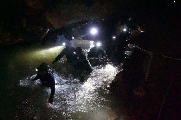 Thai rescue teams walk inside the cave complex where 12 boys and their soccer coach went missing. Photo / Supplied