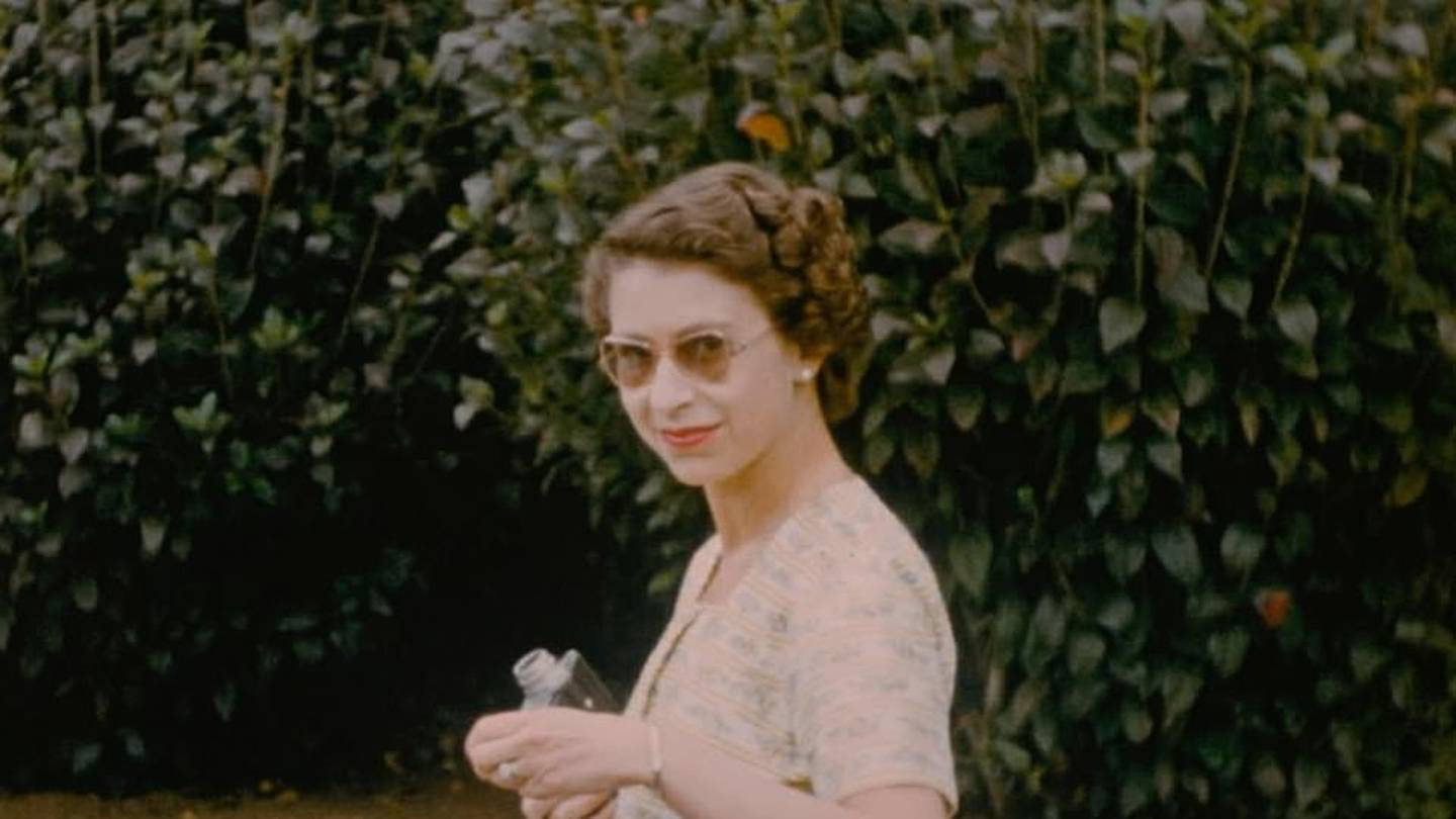 A casually dressed Queen Elizabeth II holds a Cine Camera while relaxing at the private home of NZ Governor-General at the time, Sir Willoughby Norrie on Christmas Day 1954. Photo / The Queen Unseen